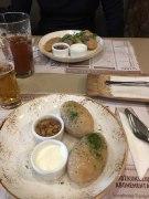 Litauisch essen, eine Art Kartoffelknödel mit Hackfleisch gefüllt, dazu Sauerrahm und Speck.